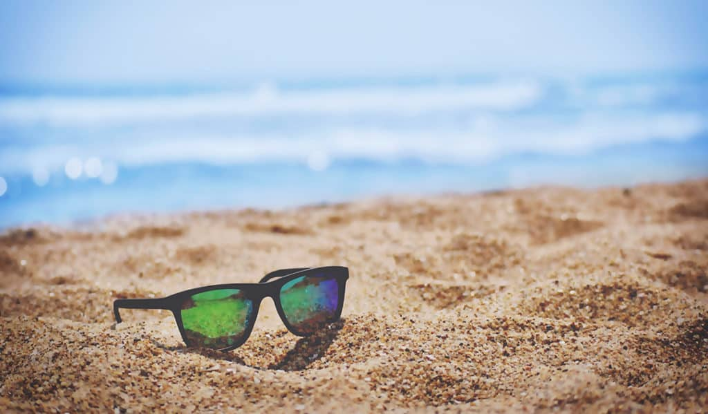 Image of sunglasses on a beach during summer