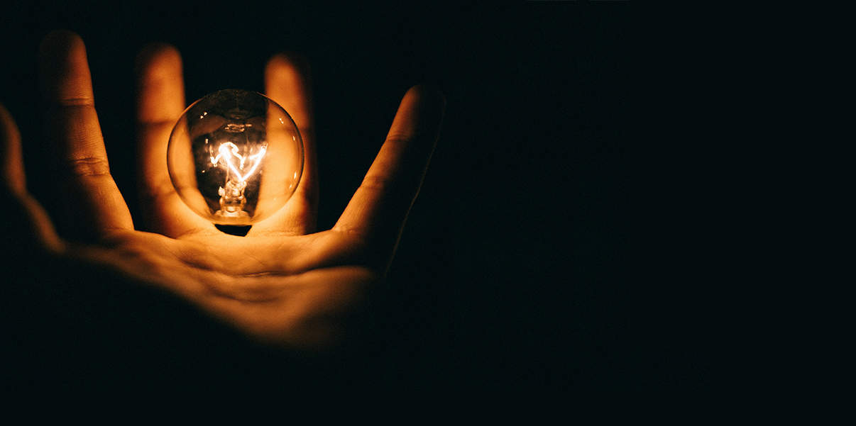 Image of a hand holding a lightbulb in darkness