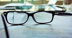 Image of glasses on a pile of paper contracts
